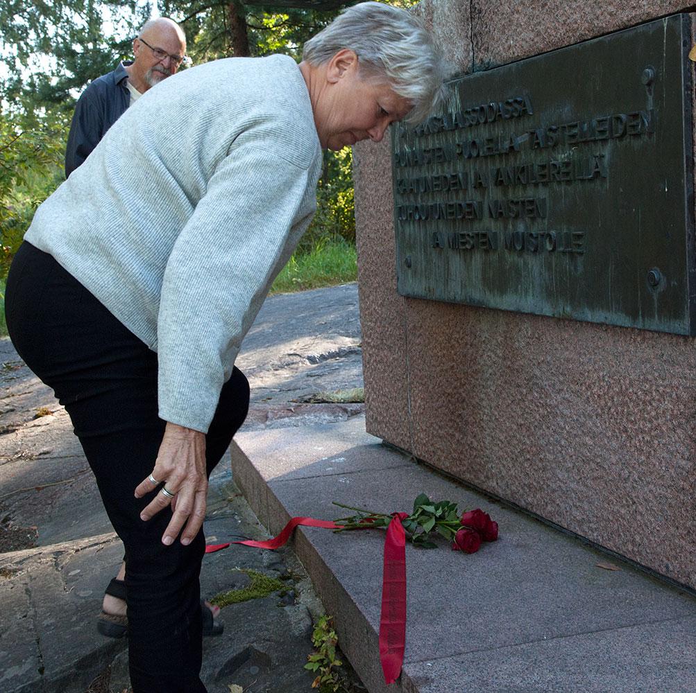 Lotta Durgé lägger ner blommor vid monumentet Crescendo.